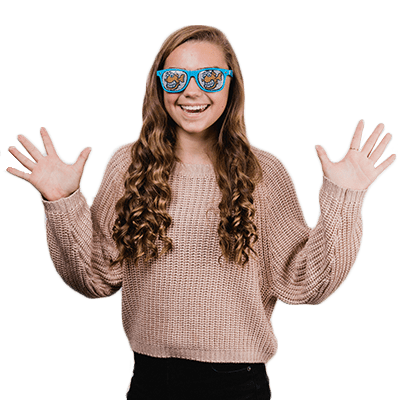 young girl, patient at Fishbein Orthodontics, straight white teeth, hands up, curly brown hair, blue sunglasses with Fishbein Orthodontics
